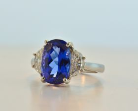 Oval Tanzanite 4.74ct (H) set in platinum with Half moons